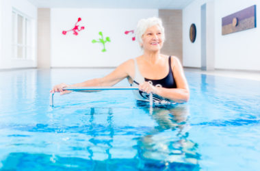 Senior woman in underwater gymnastics therapy with sliding machine